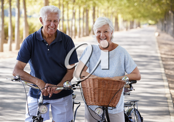 Portrait Of Smiling Senior Couple Cycling On Country Road