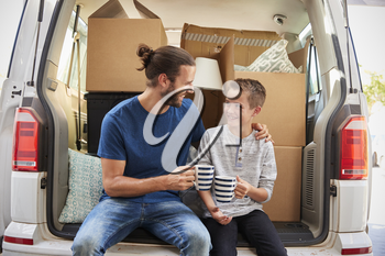 Father And Son Take A Break In Back Of Removal Van On Moving Day