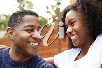 Middle aged black dad and teenage daughter smiling at each other, close up