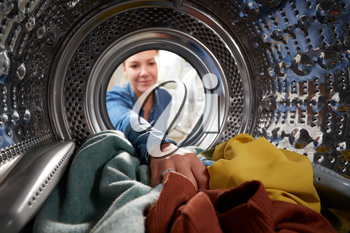 View Looking Out From Inside Washing Machine As Young Woman Does Laundry