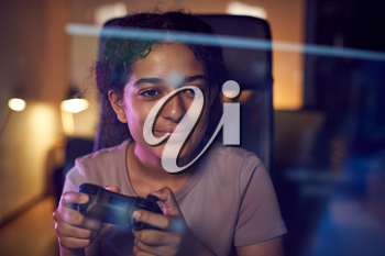 Teenage Girl With Game Pad Sitting In Chair and Gaming At Home With Screen Reflection