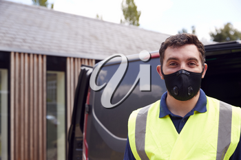 Portrait Of Delivery Driver Wearing Mask Next To Van Outside House