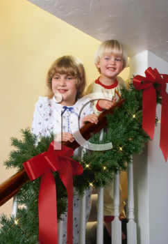 Royalty Free Photo of Excited Children on the Stairs on Christmas Morning