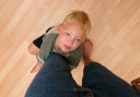 Royalty Free Photo of a Childing Hanging onto an Adult's Leg