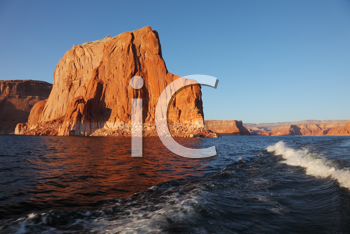 Travel voyage by boat on Lake Powell. Picturesque waves astern the ship. Sunset rays illuminate the rocks on the shore of the lake. Arizona, USA.