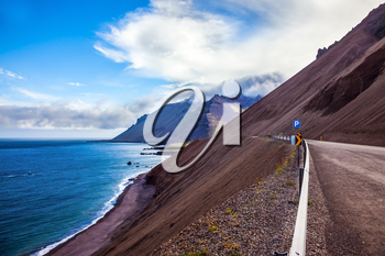 Iceland in July. The road along the Atlantic coast runs along the steep slope of cooled volcanic