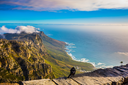 National Park Table Mountain, Cape Town. View of the Atlantic Ocean into the sunset. On the stone large crow sitting