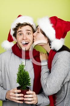 Royalty Free Clipart Image of a Couple in Santa Hats With the Woman Kissing the Man Whose Holding a Tree