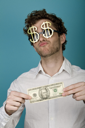 Royalty Free Photo of a Guy in Dollar Sign Sunglasses Holding a Dollar Bill