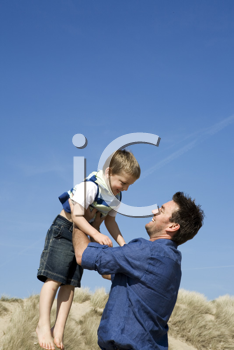 Royalty Free Photo of a Father Throwing His Child in the Air