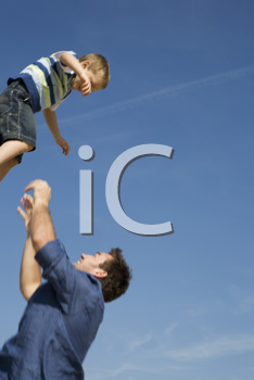 Royalty Free Photo of a Father Throwing His Son in the Air
