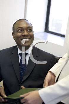 Royalty Free Photo of a Black Man Taking a File From Someone