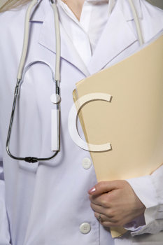 Royalty Free Photo of a Woman in a Lab Coat Holding a Folder