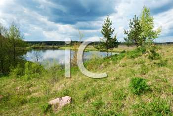 Royalty Free Photo of a Nature Scene With Water and Green Field Under a Cloudy Blue Sky