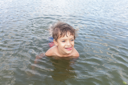 Cute little boy playing in water outdoors on summer day