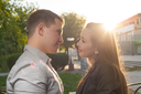 Cute Caucasian couple pose for the camera outdoors with town on background