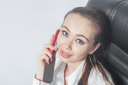 Beautiful young woman working in the room using mobile phone indoors smiling closeup