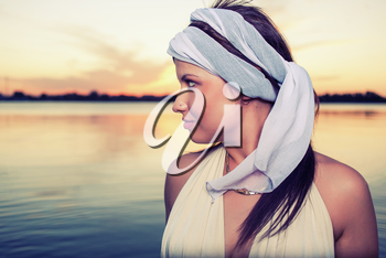 Profile view  on a retro hairstyle women against water and sunset