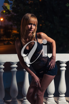 Colorized shot of a slim blonde standing near balustrade
