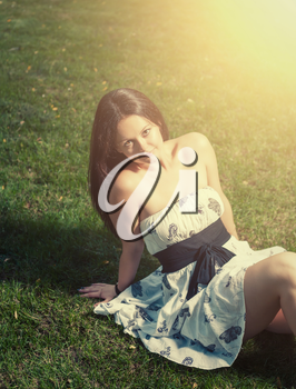 Brunette on grass and a lot of  copyspace