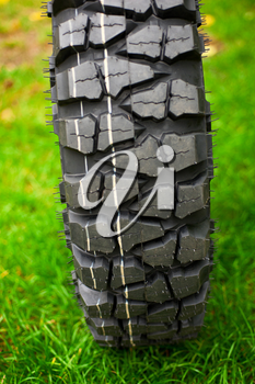 Tire at green grass background