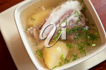 cooked soup with lamb meat, potatoes and vegetables