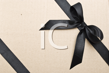 Royalty Free Photo of Black Satin Ribbon and Bow on a Cardboard Background