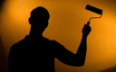 Renovation - Back lit silhouette of man and paint-roller