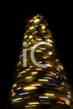 Blurred rotating New Year tree at night over black