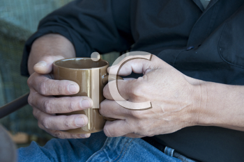 Royalty Free Photo of a Man's Hands Holding a Mug