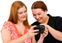 Two women holding a camera and smiling isolated over white