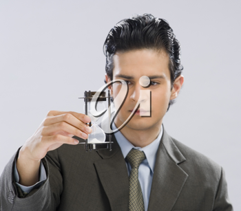 Businessman looking at an hourglass