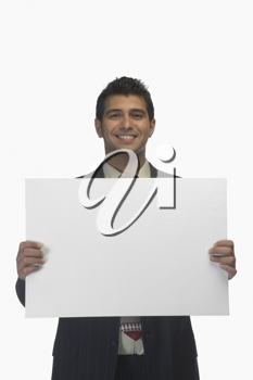 Portrait of a businessman holding a blank placard and smiling