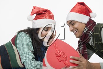 Couple lying on a floor with a Christmas present