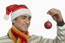 Man holding a Christmas ornament and smiling