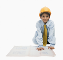 Boy dressed as an architect and working on a blueprint