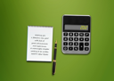 Royalty Free Photo of a Calculator and a Spiral Notepad with a Happy New Year Greeting