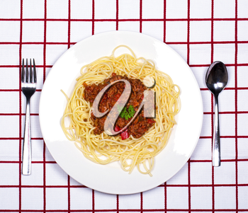 Spaghetti bolognese dinner on red and white checkered tablecloth