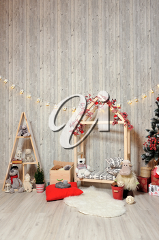 New Year or Christmas photo zone for children. Children's photo zone with a wooden house, toys, a Christmas tree and gifts in a warm light.
