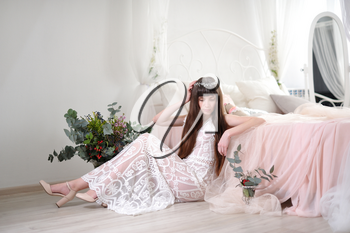 Photo of a young girl in the style of fayn art. A girl in a white translucent dress sits on the floor next to the bed and a bouquet of flowers.