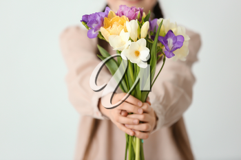Little girl with bouquet of flowers on light background
