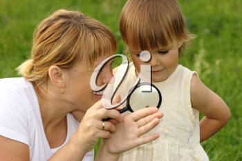 Royalty Free Photo of a Mother and Child Looking at a Snail With a Magnifying Glass