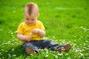 Royalty Free Photo of a Little Boy Playing With Flowers