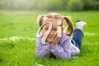 Royalty Free Photo of a Little Girl Lying on Grass