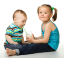 Royalty Free Photo of a Little Girl Helping Her Brother With a Drink