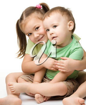 Two children (a girl and a boy) are having fun while sitting on floor, isolated over white