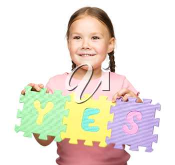 Cute little girl is holding Yes slogan, isolated over white