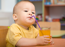Cute boy is drinking orange juice using straw