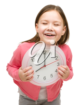 Happy little girl is holding big clock showing eight, isolated over white