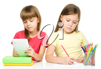 Two young girls are sitting at table, one is using tablet and the other draw with color pencils, isolated over white